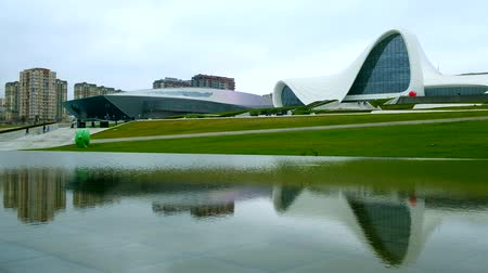 Baku, Azerbaijan - January 01, 2018: Park near Heydar Aliyev center on a cloudy day. Reflection of Heydar Aliyev Cultural Center in the water. Reflecting pool at Heydar Aliyev Centre