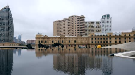 Baku, Azerbaijan - January 01, 2018: Shot of reflection of buildings in flowing water near Heydar Aliyev center, Baku, Azerbaijan. Reflecting pool in front of beautiful architecture in downtown Стоковые видеозаписи