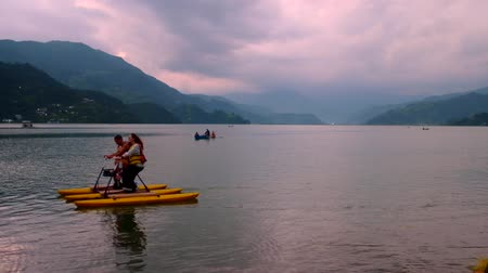 Pokhara, Nepal - 06 october, 2017: People water bicycle at Pheva lake against the background of mountains in Pokhara, Nepal