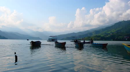 Pokhara, Nepal - 06 october, 2017: Tied boats on Pheva lake against the background of mountains in Pokhara, Nepal