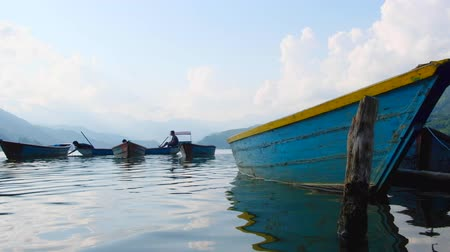 Pokhara, Nepal - 06 october, 2017: boats on Pheva lake under blue sky in Pokhara, Nepal Стоковые видеозаписи