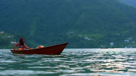 Pokhara, Nepal - 06 october, 2017: Woman sail in canoe at Pheva lake in Pokhara, Nepal Стоковые видеозаписи