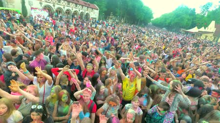 concert crowd : Kharkiv, Ukraine - May 19, 2018: People celebrating holi festival with hands waving at concert