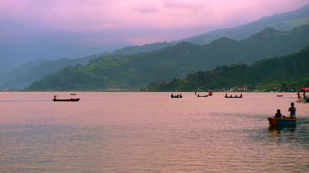 Pokhara, Nepal - 06 october, 2017: People sail in canoes at Pheva lake against the background of mountains in Pokhara, Nepal
