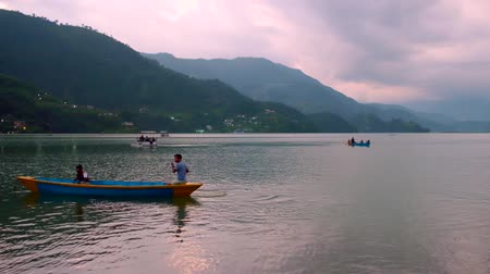 Pokhara, Nepal - 06 october, 2017: People row in canoes at Pheva lake against the background of mountains in Pokhara, Nepal