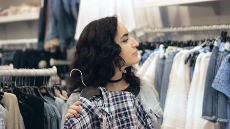 payment : Attractive brunette girl chooses dress looks in mirror. Beautiful woman brunette buys clothes in store. Pretty lady with brown hair trying on a new clothes in fitting room of clothing boutique. Stock Footage