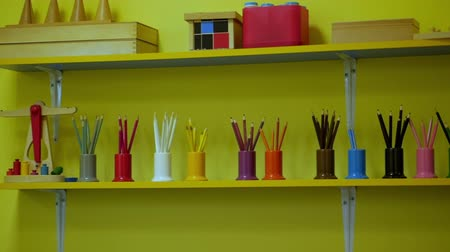 zęby : Sets of colored pencils in plastic holders-cups on the shelf.