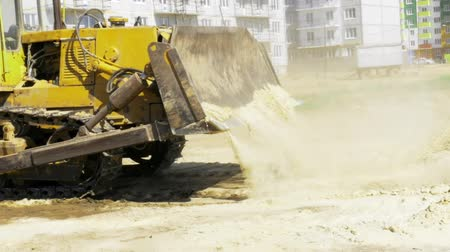 levelling : Yellow bulldozer in motion. Construction of a residential multi-apartment complex in the city. Construction. Stock video footage.