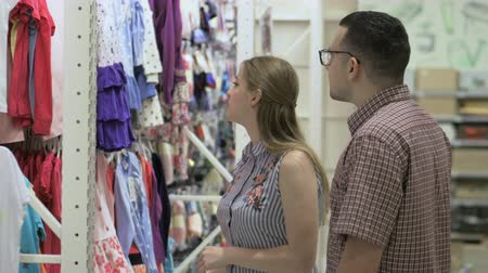 namorado : Attractive couple - young woman with her husband - chooses clothes in store. Beautiful woman considering t-shirts in the supermarket. Pretty woman buys clothes in mall. Stock video footage.