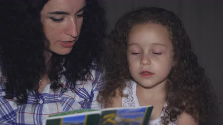 otthonos : Mom, along with a small beautiful daughter, reads with a twist of a fairy tale for the night, plunged into the story of the plot. 4K.