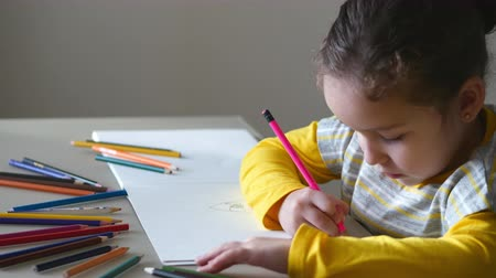 kreş : Little cute little girl draws her house with colored pencils. 4K. Stok Video