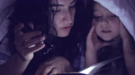 cimborák : Mom and her little daughter are reading fairy tales for the night, they are wrapped in a warm blanket and immersed in the story of the plot. 4K.