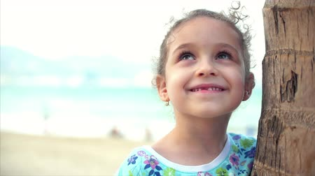 pré escolar : Happy little girl on the beach in a blue dress with a palm tree, looking at the camera, smiling and a little shy. Child, children, emotions.