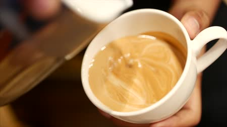 tasting : Pouring stream milk into a cup of espresso, slow motion. Close-Up. Stock footage.