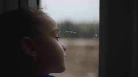 mito : Child looks at the rain behind the window. Stock Footage.
