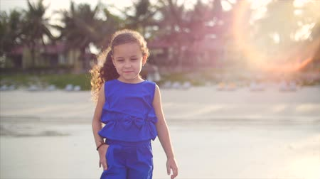 дочь : Young happy petite girl, walking near the ocean coast. Happy little girl in a blue suit, a Caucasian appearance, walking along the seashore.