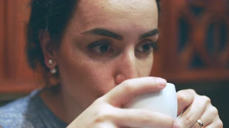 saborear : Young woman sits in a cafe, loves to smell and sip a cup of coffee