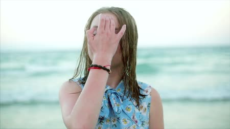 plavec : Close up portrait of European beautiful cute blonde young woman or cheerful girl smiling looking at camera, running hand through hair blowing in wind on tropical beach, slow motion Dostupné videozáznamy