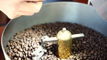 roaster : Mixing of roasted coffee. Partial removal of bad grains. The roasted coffee beans got on the mixer sorting by a professional machine. Slow motion.