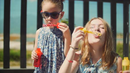 explodindo : Happy smiling Family, sisters are playing, blowing soap bubbles in the summer outdoor. Stock Footage.