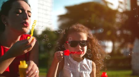 explodindo : Happy mam and child blowing soap bubbles in park. Slow motion. Stock footage. Slow motion