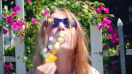 explodindo : Happy smiling teenage girl caucasian appearance, smiling looking at camera, blowing soap bubbles in summer outdoors. Close-up. Stock footage.