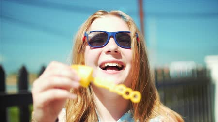 colore : Happy smiling teenage girl caucasian appearance, smiling looking at camera, blowing soap bubbles in summer outdoors. Close-up. Stock footage.