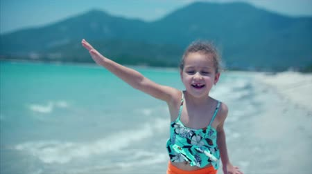 sicília : Adorable little girl runs down the beach toward her mother for a big hug and kiss. Close up shot. Stock footage