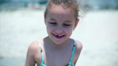 sicília : Portrait of a charming little girl in a swimsuit. A child is standing on the beach smiling, looking at the camera. Stock Footage