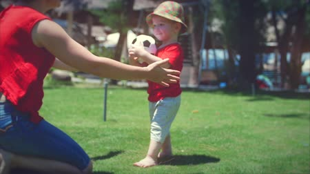 learning to walk : Cute little boy playing with a soccer ball running to his mother in a hug. Stock footage.