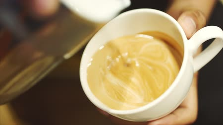 roaster : Pouring stream milk into a cup of espresso. Close-Up. Stock footage.