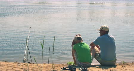 ужение : A happy father and son are sitting on the river bank, fishing, dad and son are fishing in the morning. A happy family.