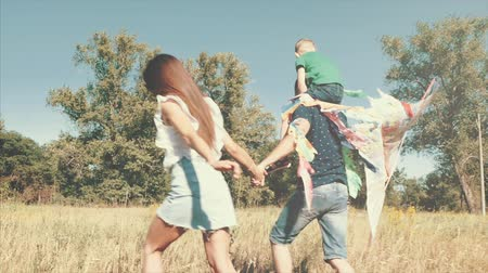 omzunda : Happy family, mom, dad and son are walking in nature, launching an air snake. Stock footage.
