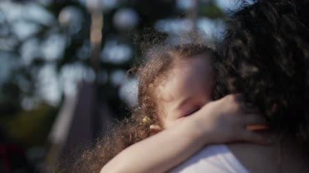 explodindo : Daughter in the arms of the mother on the street and gives her a big hug, kissing and smiling look at the camera, close-up. Slow motion.