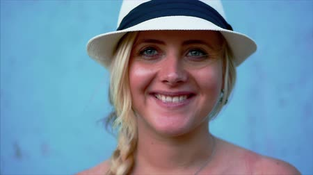 radiante : Portrait of a beautiful caucasian woman appearance, blonde in a white hat with blue ribbon, outdoors, smiling looking at camera. Cropped view, blue background.