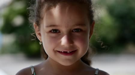 escola : Happy little girl with curly hair, with a beautiful smile and green eyes looking at the camera, happy smiling.