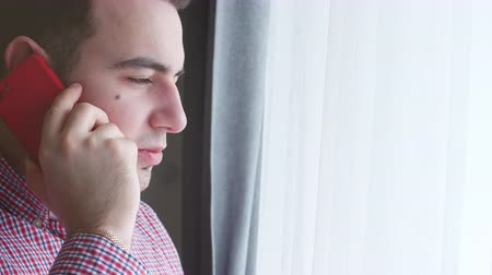 mms : Closeup of Young man in a plaid shirt speaks on a red phone while looking out the window. 4K. Stock fotage