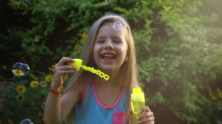 explodindo : Happy child blowing soap bubbles in park. Slow motion. Stock footage.