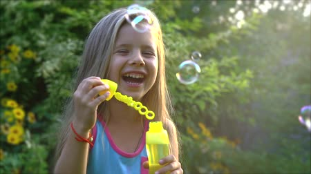 sopro : Happy child blowing soap bubbles in park. Slow motion. Stock footage.