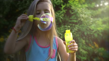 explodindo : Slow motion of a Happy little caucasian girl blowing soap bubbles in on a sunny day. Concept happy childhood or childrens games in nature. Stock Footage