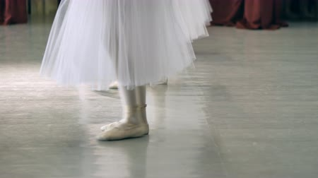 тапки : Ballet.Close-up of a girls legs in white ballet shoes during ballet training. Element of classical dance. 4K Стоковые видеозаписи