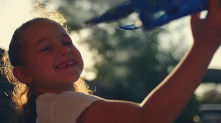 paper airplane : Happy child runs with a toy airplane on a sunset background.
