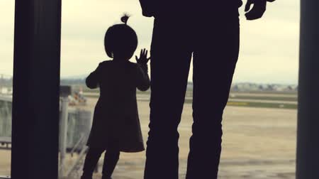 points of interest : Father and daughter looking out the window with view on airport area. Planes can be seen in the distance.