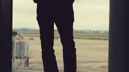 point of interest : Airport. Man looks out the window with view on airport area. Stock Footage