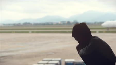 zajímavosti : Airport. Little boy looks out the window with view on airport area, he watches as the plane leaves for the take-off strip. Dostupné videozáznamy