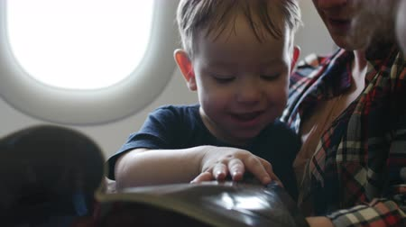 lugares sentados : Plane is flying, the little kid is sitting at the mom on the pens, lookin childrens magazine with pictures. Stock Footage
