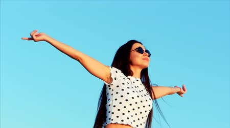растягивается : Happy free woman, rising her hands high in the blue sky, looking at the sun, feeling complete freedom in life.