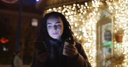 liga : Beautiful Fashionable Happy Stylish Young Woman in Brown Coat with Dark Blue Scarf and Long Dark Curly Hair Enjoys Coffee Busy with her Mobile Phone While Walking a City Street. Pretty Girl Messaging on the Smart-phone and listening to music on the backgr Vídeos