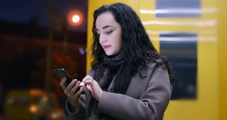 liga : Beautiful Happy Young Pretty Woman in Brown Coat with Dark Blue Scarf and Long Dark Hair Enjoys Coffee Messaging on the Smart-phone on the background of the night or evening city.
