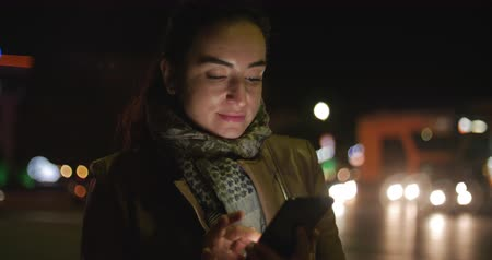 liga : Beautiful Happy Stylish Young Beauty in Brown Leather Jacket with a Dark Blue Scarf and Long Dark Hair Enjoys Messages on the Smartphone Against the Background of a Night or Evening City. 4K. Vídeos